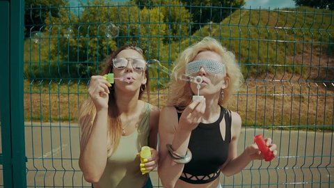 Cheerful hipster girls in sunglasses having fun making bubbles outdoors in slow motion