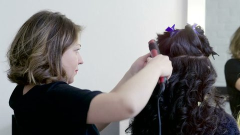 Halloween party. Hairdresser making curly hair for young brunette woman by hot curling iron. 4K