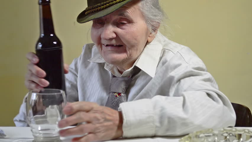Elderly woman opens the bottle of dark beer. She drink like this every day. | Shutterstock HD Video #1016822641