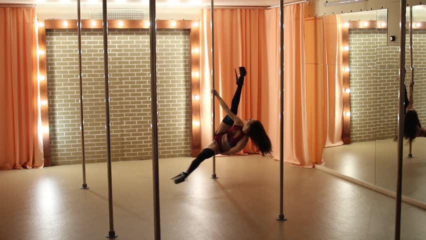 Young woman dancing on a pole, Pole dance performance by pretty girl