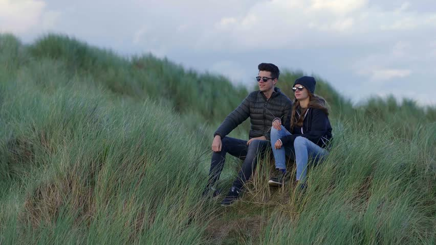 Two friends sit on the grassy dunes of Irelands west coast