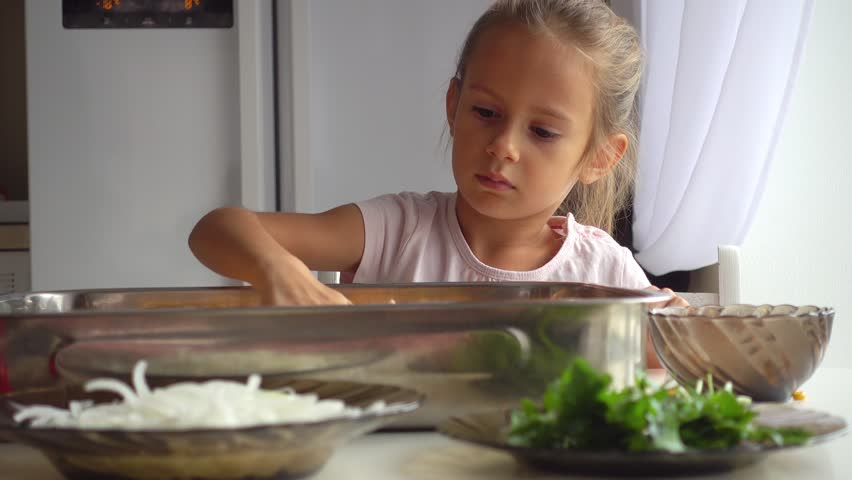 Portrait of a little girl who helps her mother in the kitchen. Daughter helps mom in pizza making 4k video. The child learns to cook food. #1016926681
