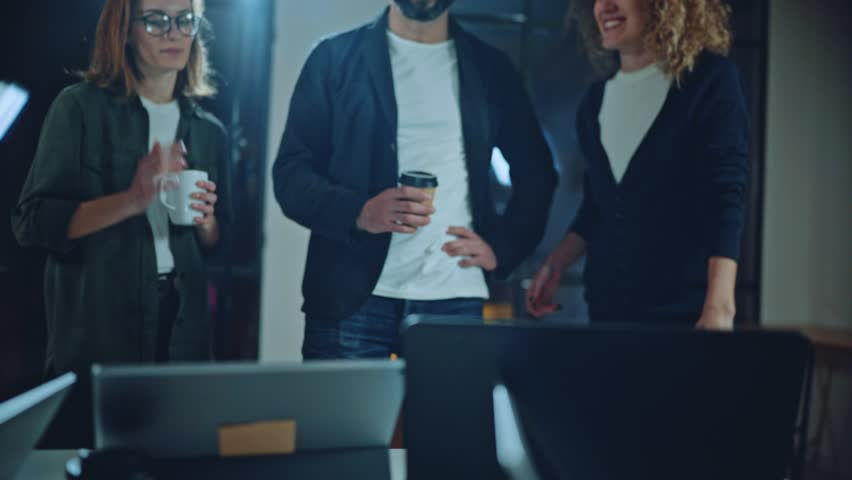 Coworkers working together in modern office.Bearded man talking with colleague and using mobile laptop while sitting at the wooden table. | Shutterstock HD Video #1016954431