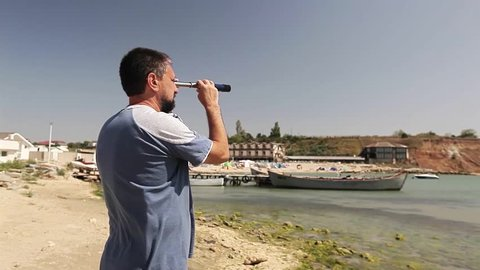 Bearded man spying with spyglass on sea shore