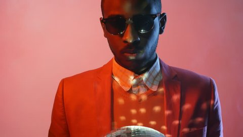 Portrait shot with red lighting: serous black man in sunglasses standing isolated on pink background and turning disco ball in his hands while looking at camera