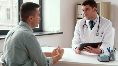 medicine, healthcare and technology concept - doctor with tablet pc computer and male patient talking at hospital