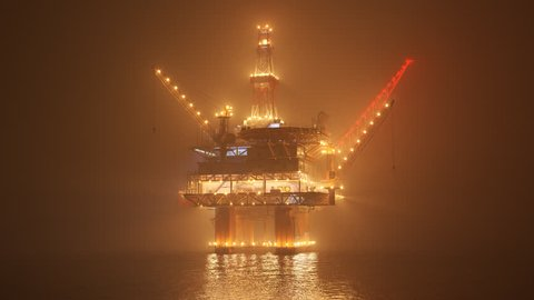 Big oil rig working on an open ocean during a foggy night. Countless lights illuminate the mist and create a reflection in the water waves. Symbol of natural environment degradation and pollution.