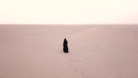 Aa woman in abaya (United Arab Emirates traditional dress) walking in the desert with smooth dawn light, as viewed from the back. Dubai, UAE.