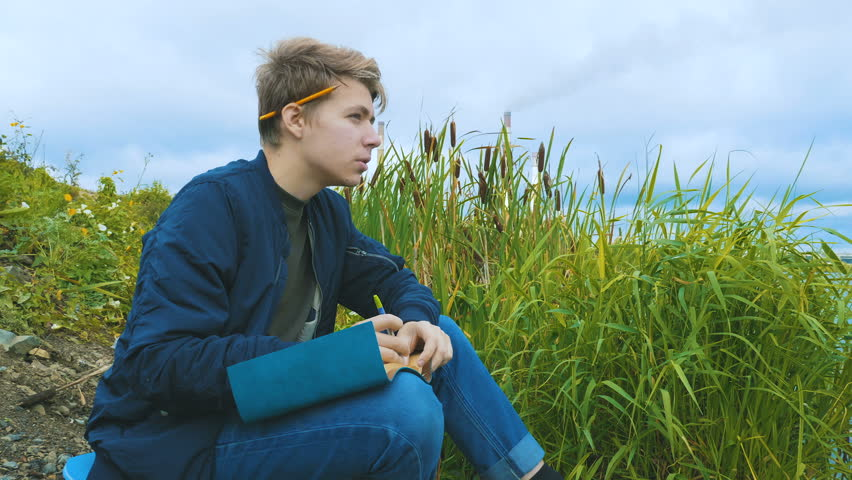 A young writer of attractive appearance sits on the river bank and writes a book. In the background, a cattail, an overcast sky and smoking pipes of a hydroelectric power station.