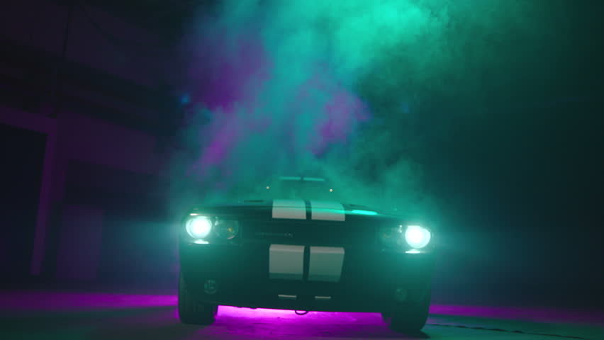 Silhouette of beautiful american muscle car on smoked dark background . Car lights on fog .  | Shutterstock HD Video #1017059281