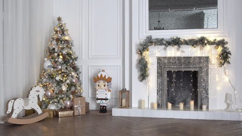 White christmas interior with New Year tree decorated with present boxes and gifts, rocking horse, nutcracker and fireplace