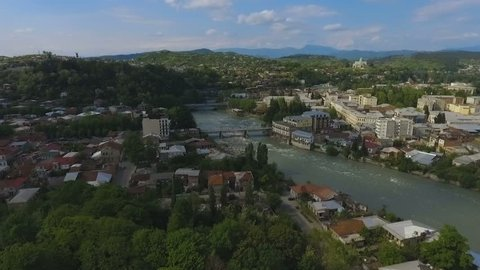 Large green Kutaisi city in Georgia aerial view, Rioni river and mountains