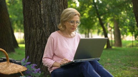 Good-looking female pensioner sitting in park with laptop and shopping online
