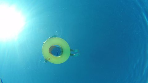 Girl floating on inflatable ring in swimming pool, view from underwater from the bottom