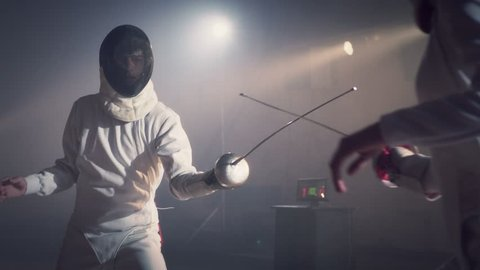 Footage video slow motion of two fencing athletes duel . Two Professional Fencers Show Masterful Swordsmanship in their Foil Fight. They Dodge, Leap and Thrust and Lunge . Shot on ARRI ALEXA in slow .