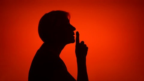 Silhouette of senior woman on red background. Female's face in profile put finger to lips making silence gesture. Black contur shadow of grandmother's half-face shush. Concept of mystery and secrecy
