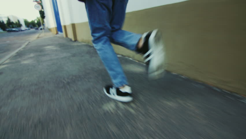 Man legs running on road in sport shoes. Guy in black and white sneakers going on asphalt city sidewalk. Close up man legs in blue jeans and sport shoes running in city