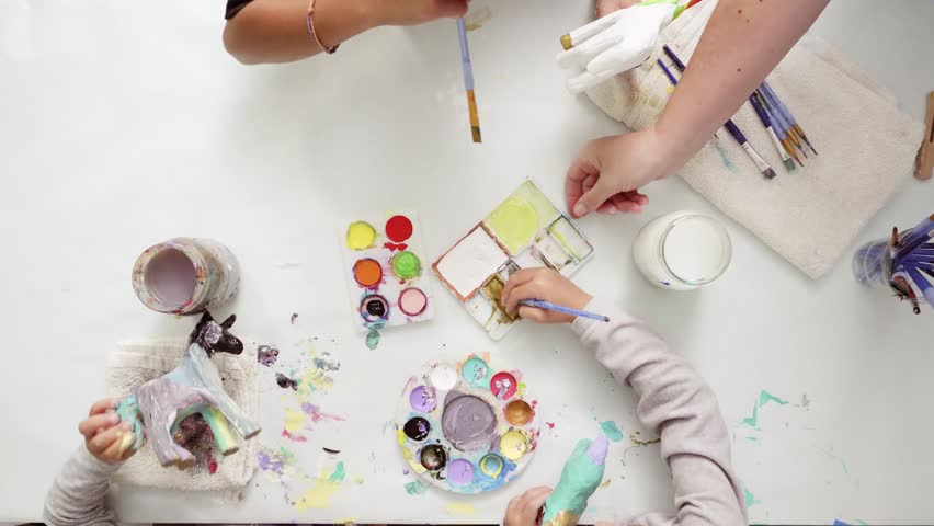 Step by step. Little girls painting paper mache unicorn with acrylic paint. | Shutterstock HD Video #1017196801
