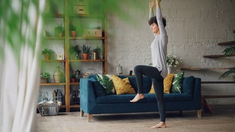 Slender young woman is concentrated on balancing exercises during personal training at home standing on floor on one leg. Well-being and sports concept.