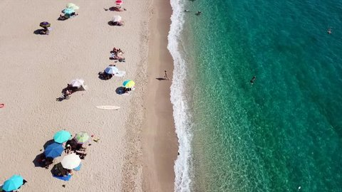 Aerial drone bird's eye view video of popular beach of Karavostasi with beautiful clouds and turquoise sandy beach full of sunbeds at summertime, Epirus, Ionian, Greece