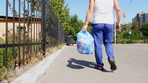 back view, man is carrying a package of garbage in his hands, take out trash. summer hot day. ecology. separation of debris, cleanliness of the environment