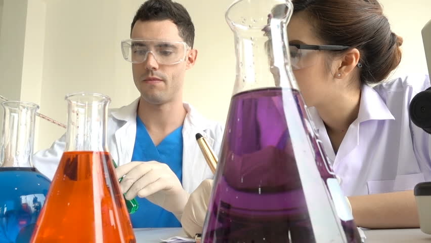 Male and woman in cover glasses research scientist uses micropipette filling test tubes analysis and recording the result in laboratory in white background,Teamwork scientist,Education and Experiment,