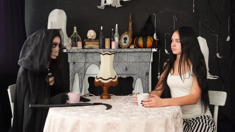 Young brunette woman drinking tea having casual conversation with woman in spooky scary Death Ripper Halloween costume