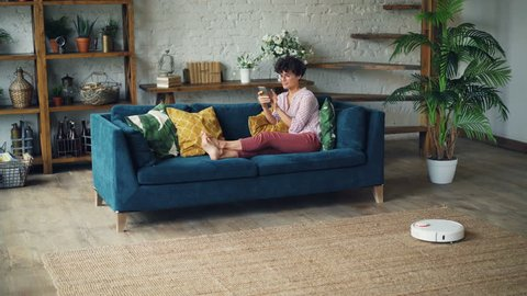 Smiling young lady house owner is sitting on sofa in living room using smartphone while robotic hoover is cleaning floor doing domestic work. Inventions and everyday life concept.
