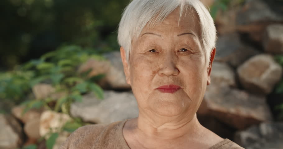 Happy old panasian woman sitting in park, looking at camera and smiling - portrait 4k | Shutterstock HD Video #1017320881