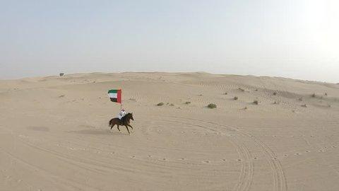 Emirati man riding Horse in the desert holding UAE Flag