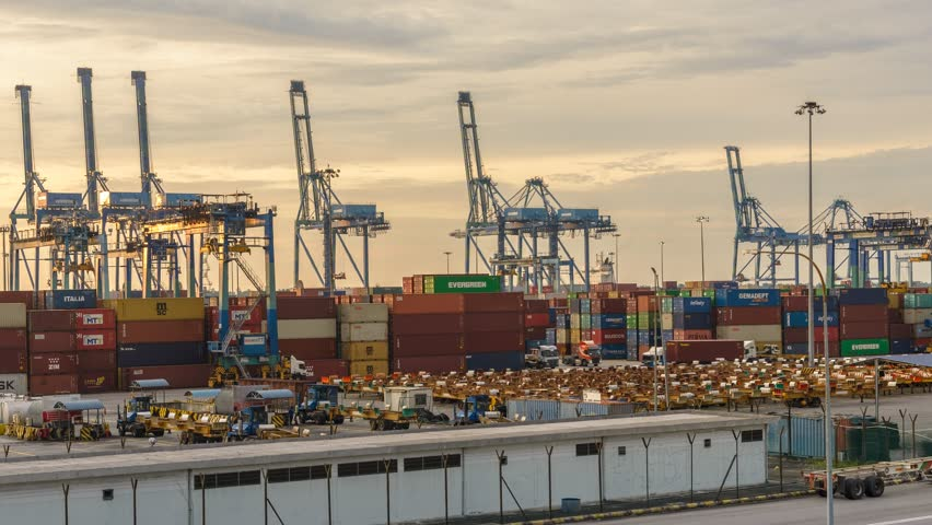 Busy container port during sunset. West Port, Malaysia. Timelapse Zoom Out