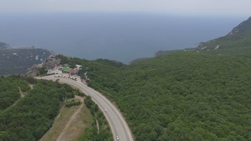 Shooting from the air of South-coastal highway Sevastopol-Yalta. Crimean mountains, tourism destinations observation deck above village Laspi, beaches and houses.