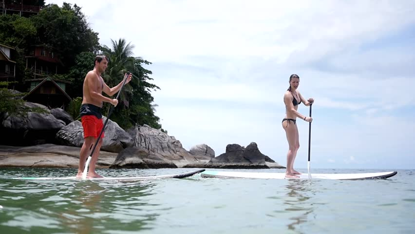 Young male and female learn to stand on paddle bordes help paddles. HD, 1920x1080, slow motion