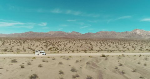 AERIAL - A brown camper van in the distance drives from left to right through the image while being passed by a small black car in the middle of the Mojave desert on a clear and blue day