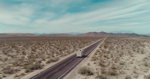 AERIAL - A drone follows a brown RV in the Mojave desert on a sunny day with mountains in the back and tumbleweed next to the road