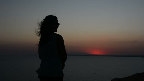 silhouette of a woman who moves against a sunset background, a lady dances on the sand in the evening, her hair fluttering in the wind