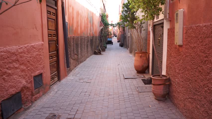 Moroccan orange narrow street alley in local neighbourhood with plants outside doors arabian traditional architecture | Shutterstock HD Video #1017395701