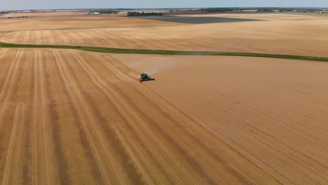 An aerial flyover of a farmer in a combine harvesting a wheat field.