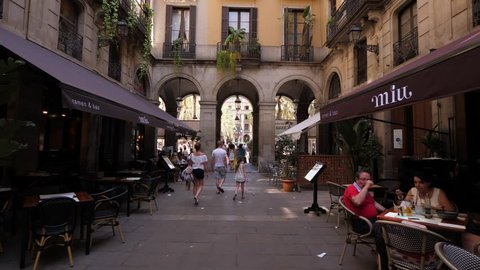 BARCELONA, SPAIN - AUGUST 13, 2018: Discovering of Gothic Quarter of city, POV walk at small passage to Royal Plaza, unidentified tourist family come ahead, people rest at cafe. Lovely old city