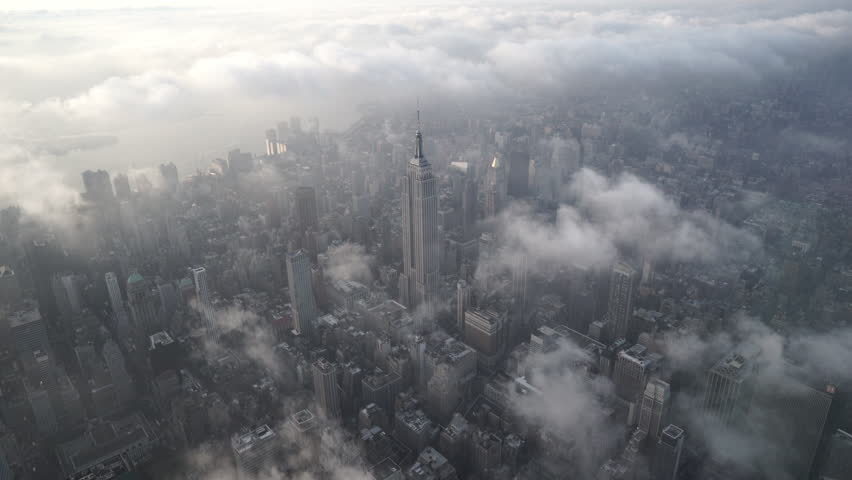 New York City Circa-2015, aerial view flying over Midtown Manhattan, featuring the Empire State Building, with low level clouds at sunrise | Shutterstock HD Video #1017553471