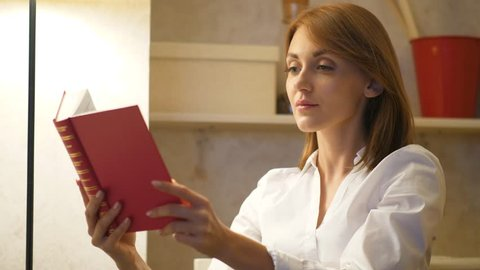 Woman read red vintage book at home alone. Cozy home evening concept