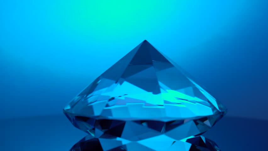 Diamond rotating at its point reflects blue light   Shutterstock HD Video #1017661171