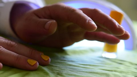 Man in salon painting nail polish manicure on nails close up hands