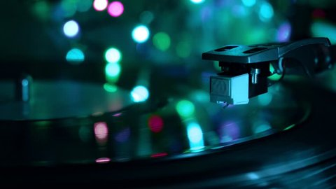 Vinyl record player  needle drops  night cold neon lights background  close  up macro shot  neo noir atmosphere concept