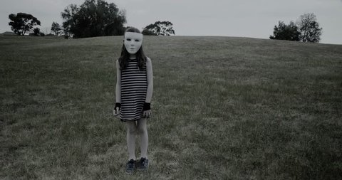 Young girl in white halloween masks tilts head looking creepy while standing in a park