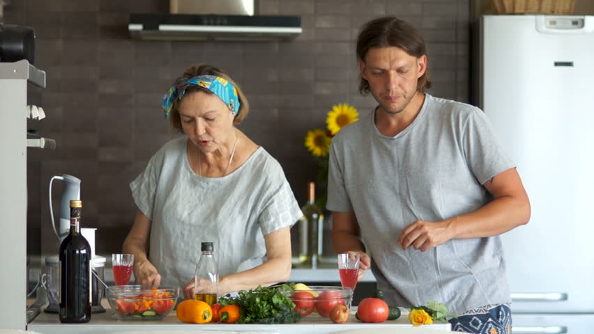A couple with an age difference prepare the salad in the kitchen, they relax to the music and drink wine from the glasses
