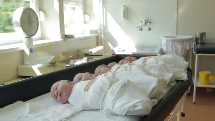 Newborn infants lying on table in maternity ward. Hungry baby old two days crying and other babies sleeping. Baby scales measured in the background. Gynecology. Shallow depth of field, childcare.30fps
