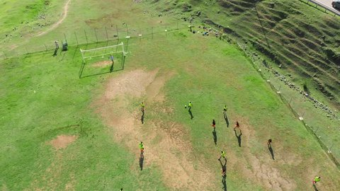 Authentic aerial video of children playing football on the river bank, countryside. Teenagers playing soccer grass field, drone flight.