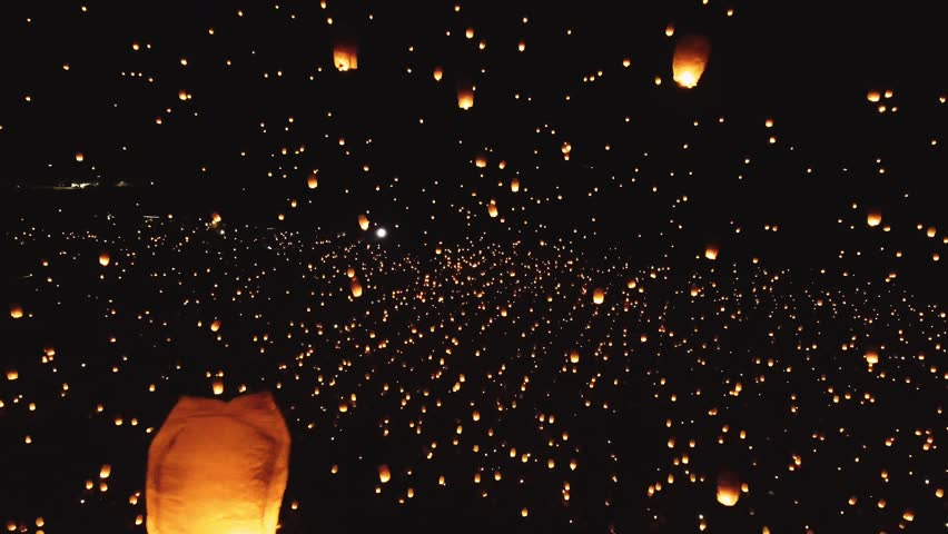 Drone footage of thousands of glowing lanterns flying across screen. Beautiful floating lanterns light the night sky as thousands of people gather to let their wishes fly. | Shutterstock HD Video #1018036621