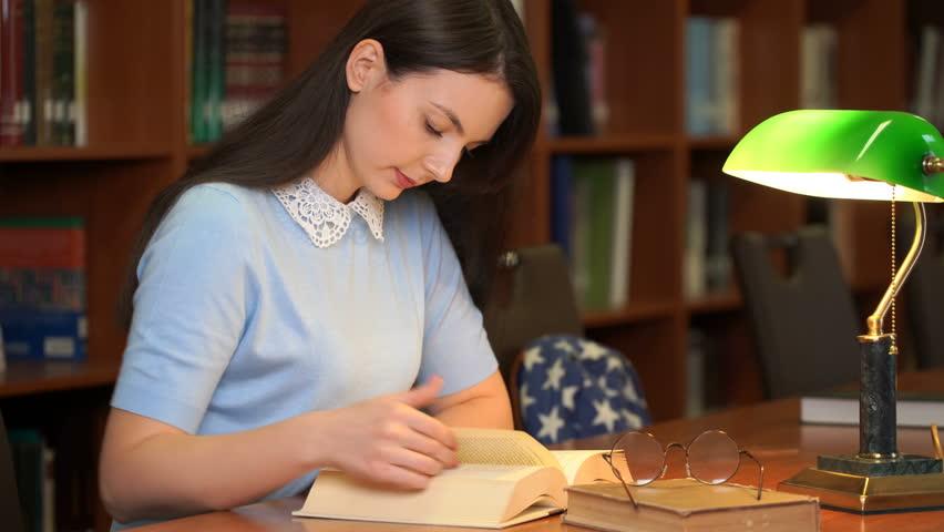 Footage portrait of schoolgirl doing their homework in library. Pretty woman read book in library office. 4k education video | Shutterstock HD Video #1018037401